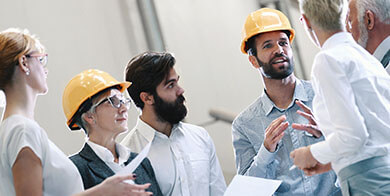 Team of experts on a construction site discuss construction details.
